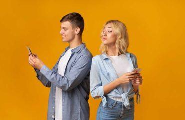 uomo chatt al cellulare e donna guarda